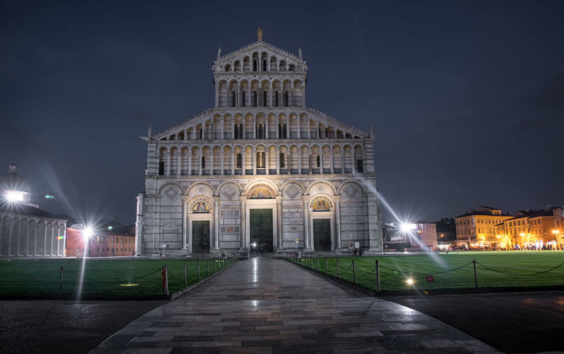 Empty footpath leading towards pisa cathedral at night
