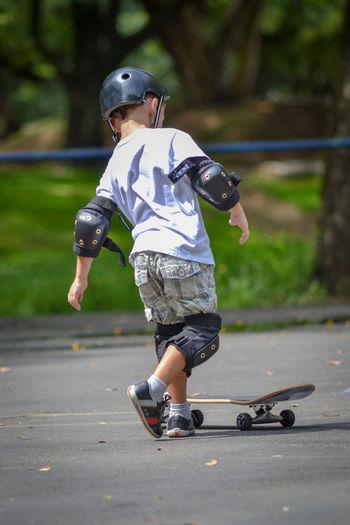 Rear view full length of boy skateboarding on road