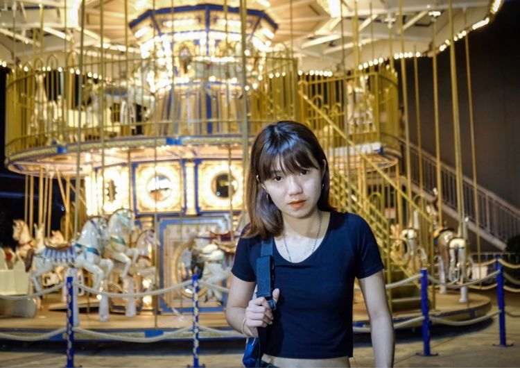 Portrait of smiling woman standing against illuminated carousel