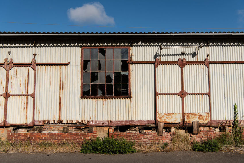 Old station building and a cloud... Station Building Train Station Railway Station Old Decay Rusty Simplicity Minimalism Cloud Window Shattered Glass Architectural Detail Sunny Power In Nature Travel Abandoned History Corrugated Iron Sky Architecture Building Exterior Cloud - Sky Grass Closed Shutter Door Closed Door Corrugated Gate Entrance