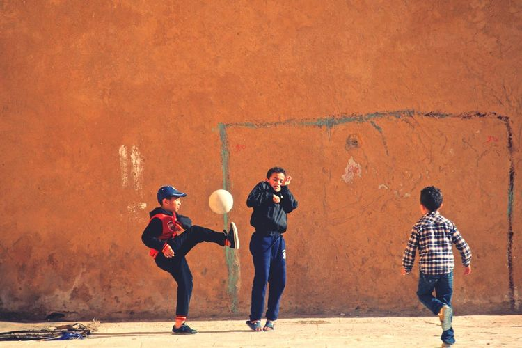 Kids playing football Kids Having Fun Kids Playing Kidsphotography Kids Football Game Football Fever MoroccoTrip Summertime Morocco Football Morocco 🇲🇦 EyeEm Selects Full Length People Child Boys Friendship Males  Lifestyles Standing Childhood Casual Clothing Women Leisure Activity Sport Wall - Building Feature Group Of People Offspring Teenager Girls Be Brave