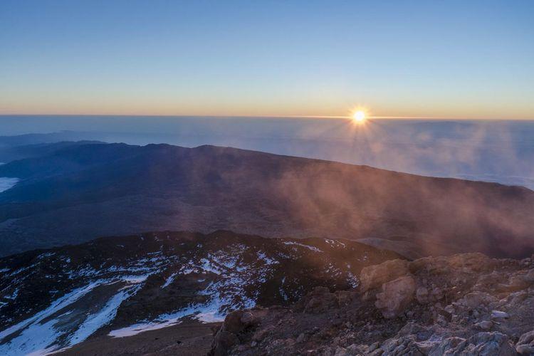 Sun shining over mountain