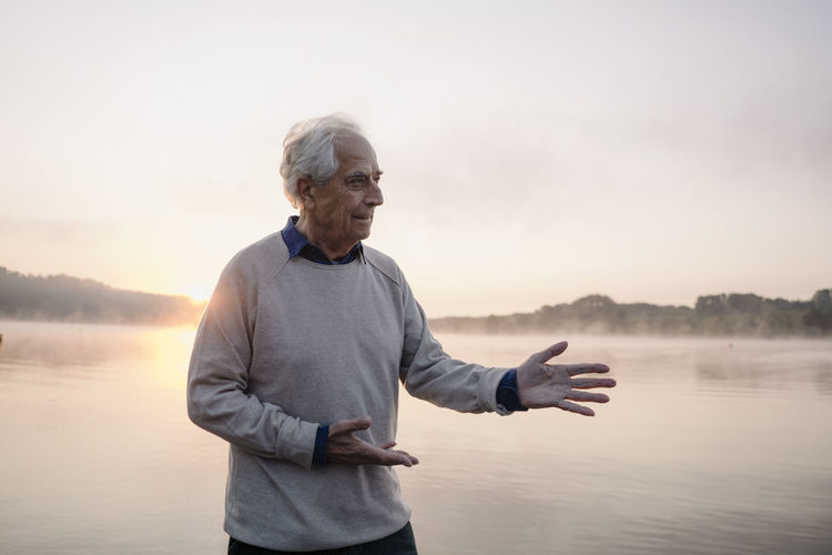 Man standing by lake against sky during sunset