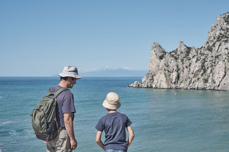 A boy and his grandfather standing on the shore of the bay, talking, looking at the rock.