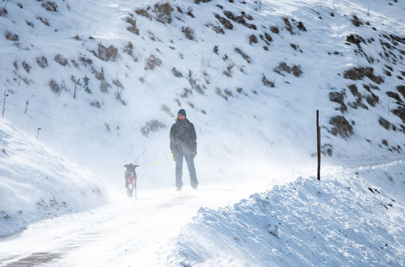 Mid adult woman with dog standing on snow covered mountain