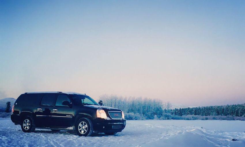 Car on snow field against clear sky