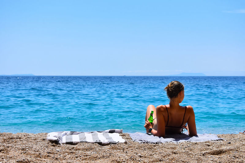 Rear view of woman relaxing on beach against sky
