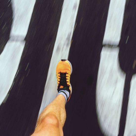 Road Running Running Shoes orange Human Hand Real People Holding Men Day Leg One Person Work Tool Human Body Part outdoors