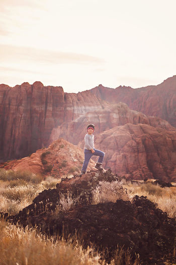 Full length of man standing on rock against mountain