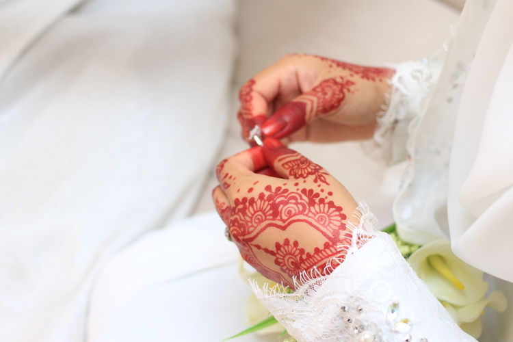 Midsection Of Bride Hands With Henna Tattoo During Wedding