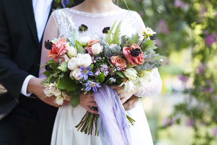 Midsection of bride and groom with flowering bouquets
