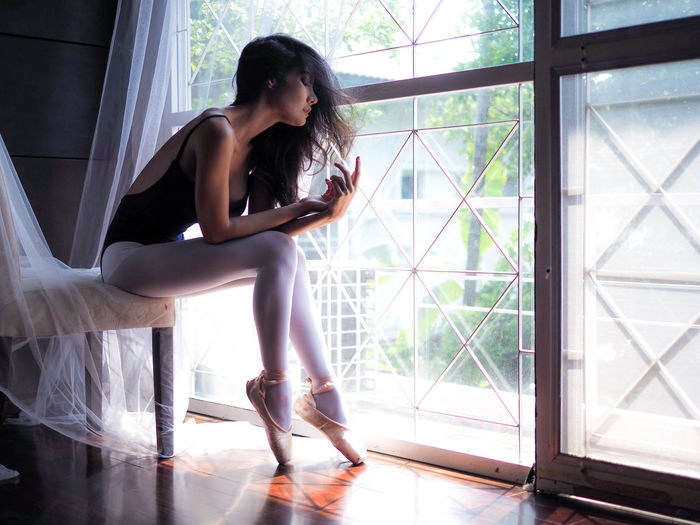 Side view of ballet sitting by window at home