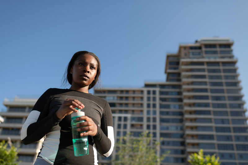 Low angle view of young woman standing against clear sky
