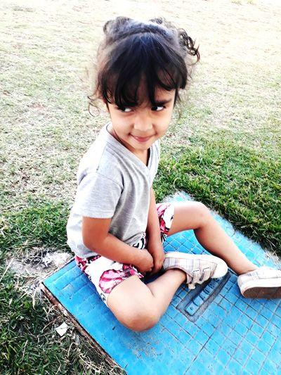 Thoughtful girl sitting on grassy field