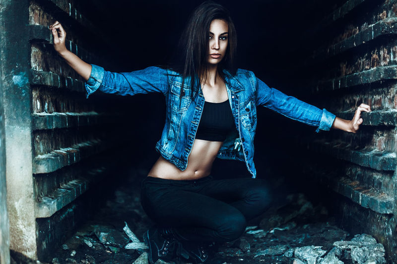 Portrait Of Confident Young Woman Wearing Denim Jacket While Crouching Amidst Walls
