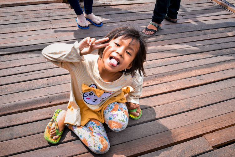 High Angle View Childhood Day Casual Clothing Real People One Person Looking At Camera Child Sitting Outdoors Leisure Activity Women Footpath Sunlight Mouth Open Nature Portrait Lifestyles Innocence Girls