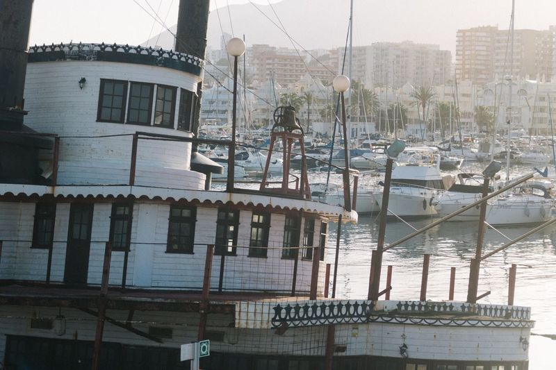 Sailboats moored in river against buildings in city