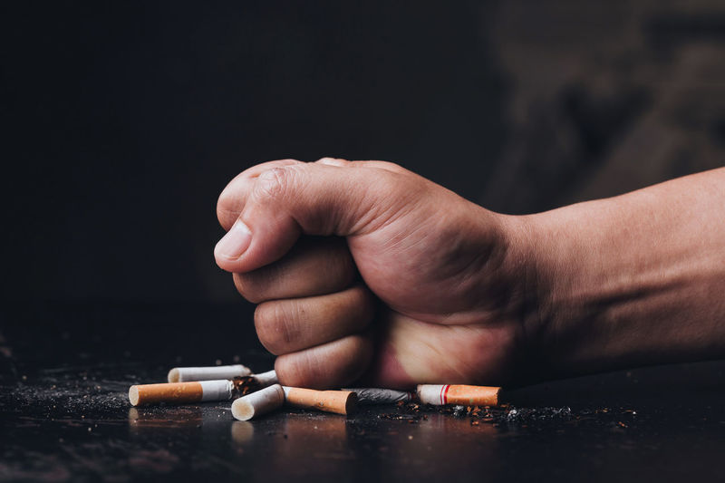 Cropped hand of person crushing cigarette against black background