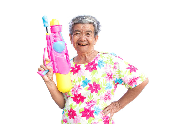 Portrait Of Happy Senior Woman Holding Water Gun Against White Background