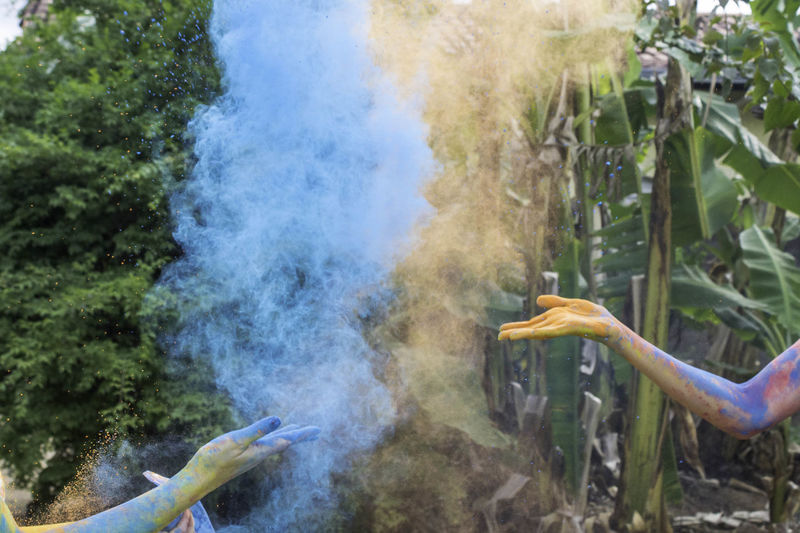 Cropped image of hands throwing powder color during festival