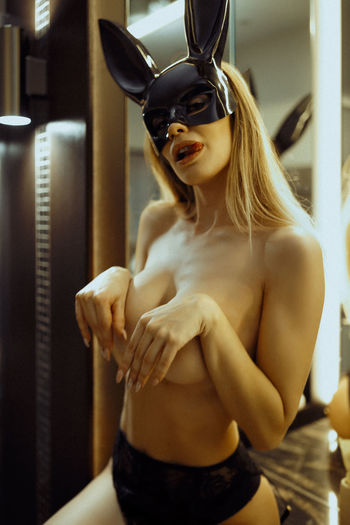 Portrait of topless young woman wearing eye mask at home