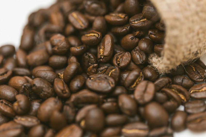 Coffee beans in a bag on a white background Abundance Black Peppercorn Brown Close-up Coffee - Drink Coffee Bean Coffee Cup Food Food And Drink Freshness Group Of Objects Healthy Eating Indoors  Large Group Of Objects No People Raw Coffee Bean Roasted Roasted Coffee Bean Sack Scented Selective Focus Still Life Table