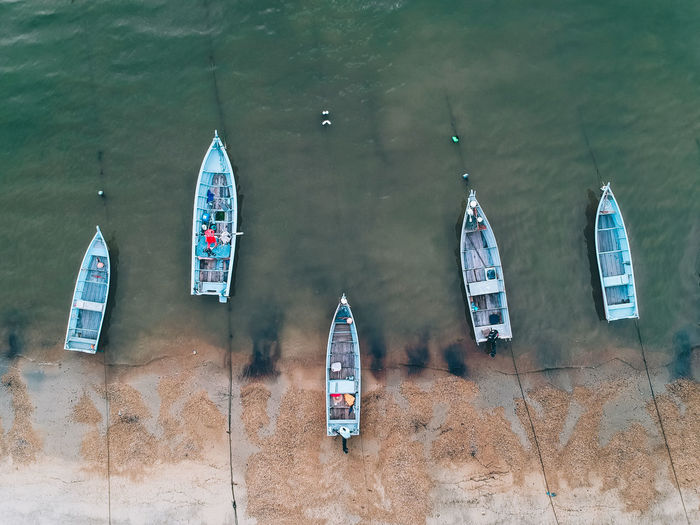 High Angle View Of Boats Moored On Shore At Beach