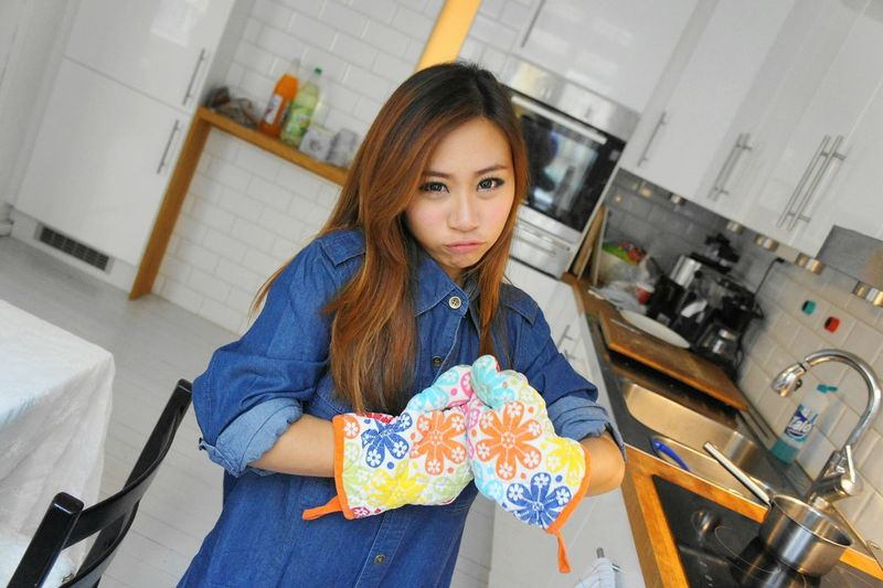 Portrait of woman wearing protective glove in kitchen