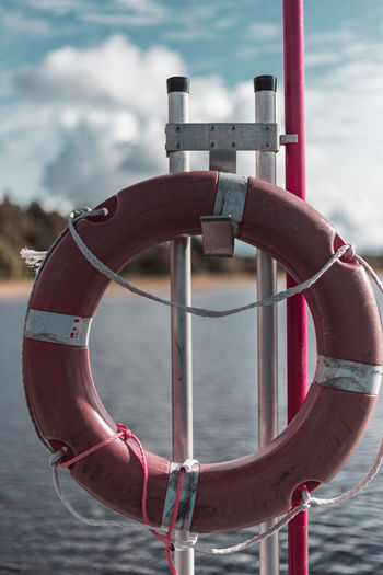Close-up of lifebelt in sea against sky
