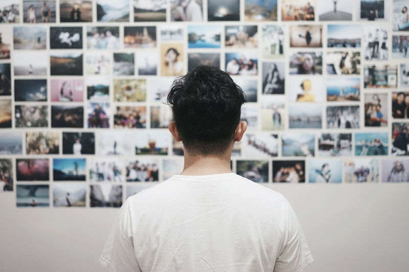 Rear view of man standing against photographs on wall