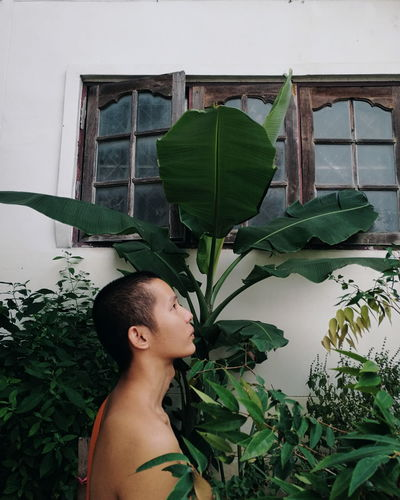 Side view of monk standing amidst plants by house