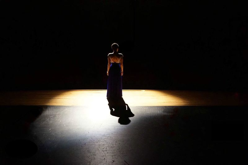 Full length rear view of woman standing on illuminated stage