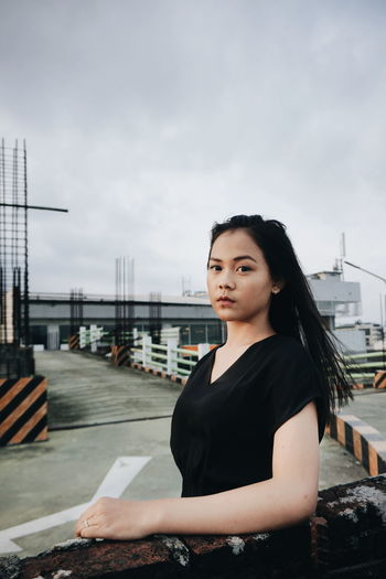 Beautiful young woman standing against sky in city