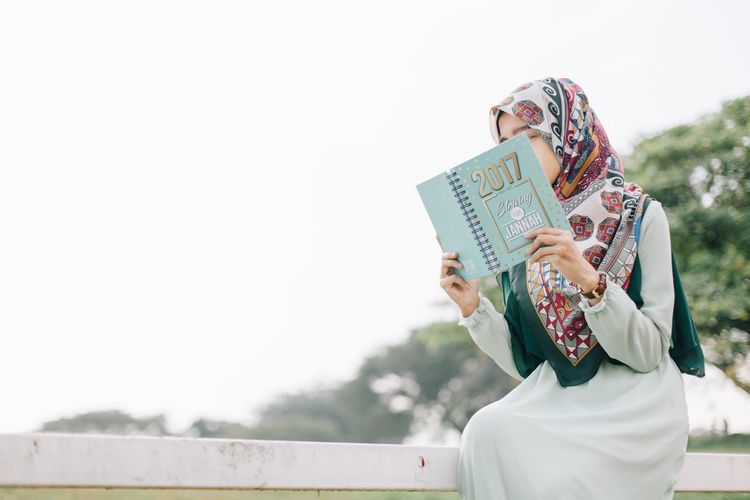 Low angle view of woman reading book against sky