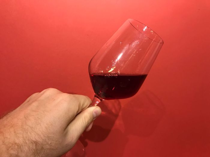 Holding a glass of red wine against a red wall Lifestyle Red Wall Wine Glass Wineandmore Winetasting Wine Tasting Wine moments Wineglass Food And Drink Wine Red Wine Holding One Person Red Body Part Human Finger Red Background Lifestyles Indoors