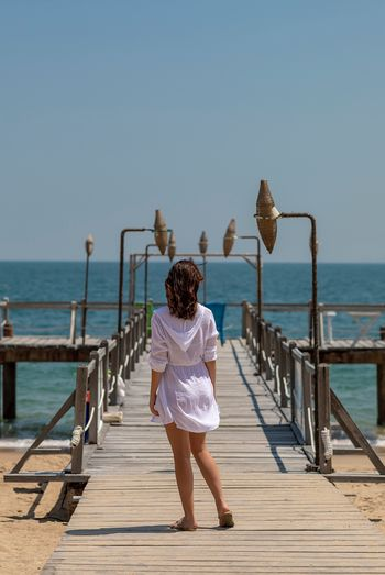 Rear view of woman on pier over sea against sky
