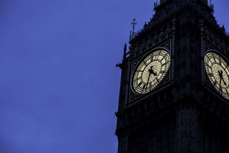 Low angle view of big ben against clear blue sky at dusk