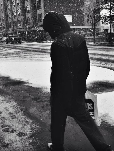 A Streetphoto_bw in the Snow of a man walking with his shopping bag. Blackandwhite IPhoneography