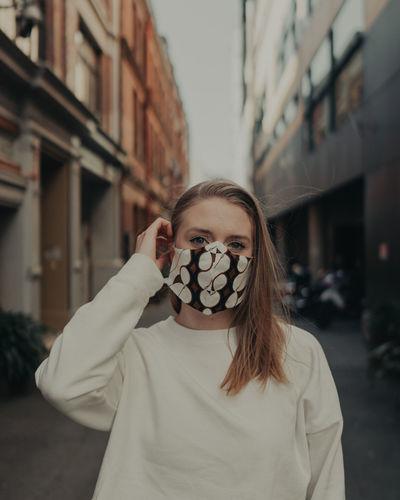 Portrait of beautiful woman wearing mask standing on street in city