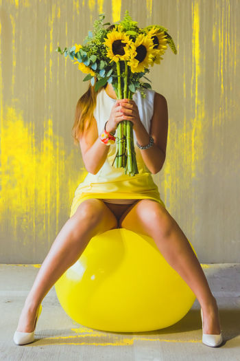 Woman holding sunflowers while sitting on yellow fitness ball