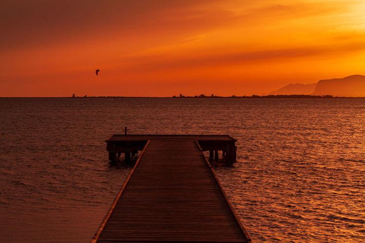 Wooden pier over sea against orange sky