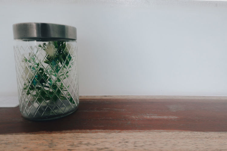 Close-up of glass jar on table against wall