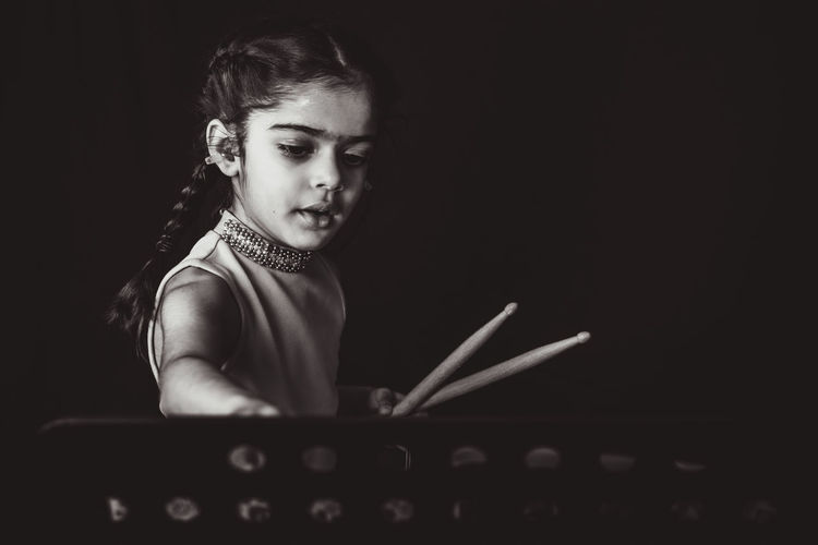 Girl playing musical instrument against black background