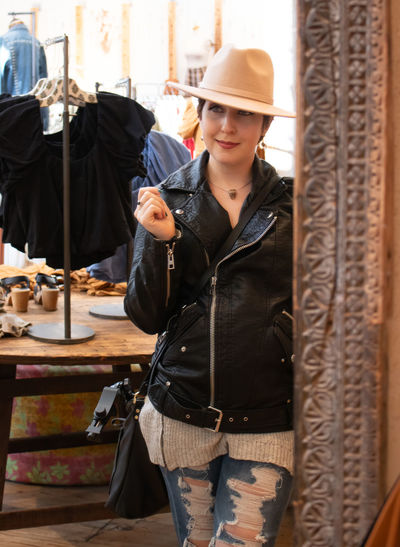 Smiling woman wearing hat looking away at boutique