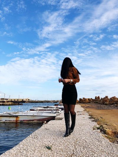 Young woman standing at shore against cloudy sky