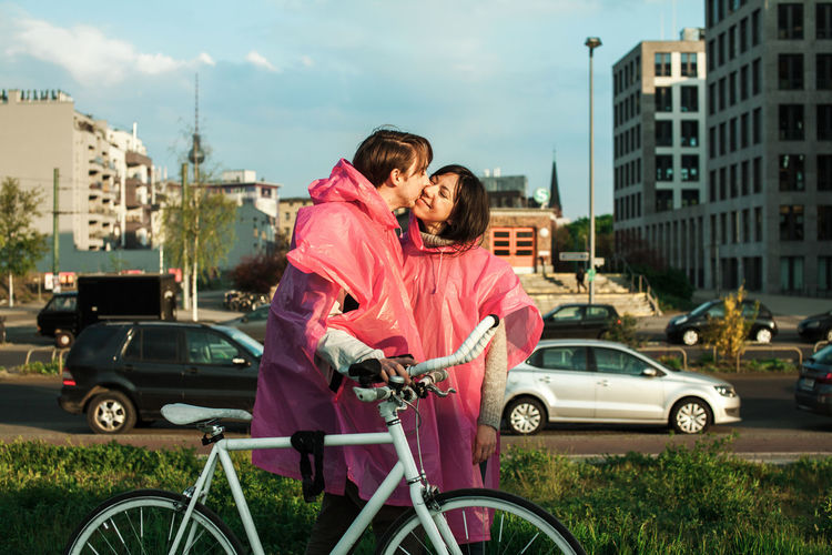 Couple wearing one piece two people rain poncho walking on a sunny after rain city Couple Kiss Love Romance Bonding Bycicle City Friendship Happiness Love Outdoors Pink Color Smiling Togetherness Two People