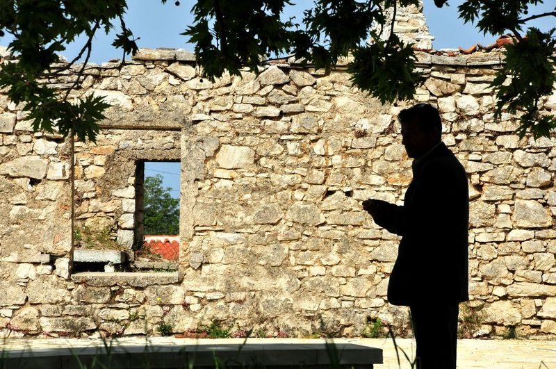 Side view of silhouette man standing against brick wall