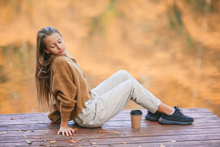 Woman looking away while sitting on wood