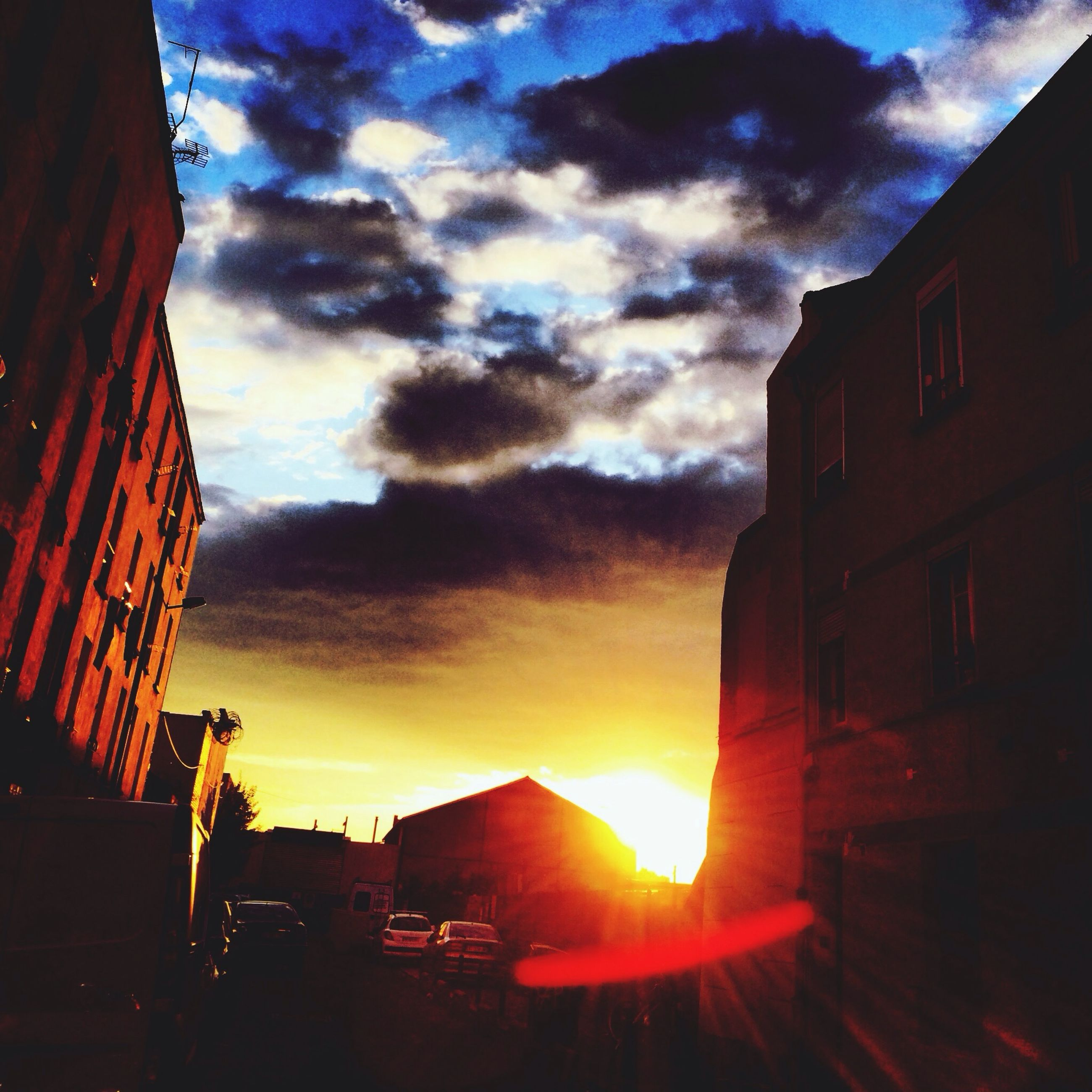 building exterior, sunset, architecture, built structure, sky, cloud - sky, sun, sunbeam, house, sunlight, residential structure, orange color, cloud, cloudy, residential building, city, building, car, outdoors, low angle view
