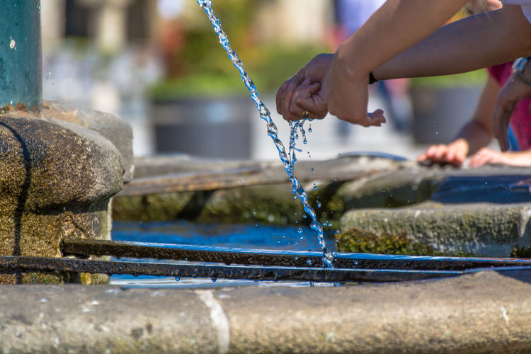 Cropped image of people washing hands in fountain on sunny summer day